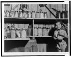Jack Delano. Dolores Harris daughter of FSA (Farm Security Administration) client George Harris, with canned food prepared by her mother Dameron Maryland