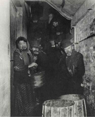Jacob Riis. (El ambiente lúgubre de esta escena en las barriadas neoyorkinas de fin del s. XIX se subraya con la escasa luz)
