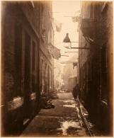 Thomas Annan Plate 13- Close, No. 80 High Street. Children loiter in an alley close to an overflowing gutter