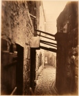 Thomas Annan Plate 8- Close, No. 83 High Street. A tenement is supported by struts from a house built in a back court.