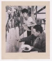 """Fotógrafo no identificado. Diego Rivera con su asistente Violeta trabaja en el mural """"La Gran Ciudad de Tenochtitlán"""" en los pasillo de Palacio Nacional, Ciudad de México (1945)"""