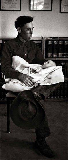 Ralp Pickering carga a su bebé de cinco semanas mientras espera al Dr. Ceriano; es el primer paciente del día. Pickering, guía a caballo de turistas que visitan las majestuosas Rocky Mountains, viajó desde un rancho para llegar al consultorio.
