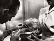 El Dr. Ceriani usa una jeringuilla para irrigar la cera en el oído de un anciano para mejorar su audición.
