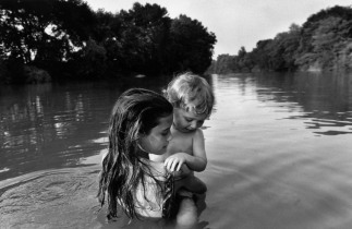 CANADA. Lambton County, Ontario. Two-year-old Isaac TOWELL is carried into the Sydenham River by his older sister Naomi to introduce him to water. 1996.