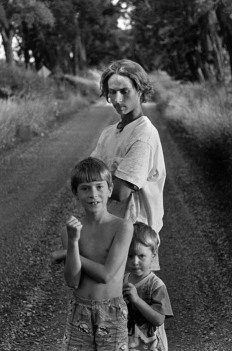 CANADA. Lambton County, Ontario. 1997. Moses (back), Noah (centre), and Isaac (bottom) TOWELL stand on the road that runs in front of their home in rural Ontario. ©Larry Towell/Magnum Photos