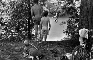 "CANADA. Lambton County, Ontario. 1995. Naomi TOWELL swings out over the Sydenham River on a rope suspended from a maple tree. Her brothers Moses (left), Noah (right), and Isaac (rear) look on. The rope is in a very small park near their home. The river also flows by their house. The family had ridden bicycles to ""Shetland Park"" on a Sunday afternoon, stopping to visit the ELLIOT family on the way home. The ELLIOTS find the river to be too dirty to swim in and have an above ground swimming pool. The photographer grew up on the Sydenham River and has swam in it all his life believing that the river is clean enough for swimming. A little dirt never hurt anyone. ©Larry Towell/Magnum Photos"