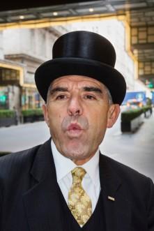 GB. England. London. The Savoy Hotel. Doorman, Tony Cortegaca whistling for a cab. 2016.