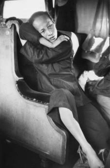 """Province du Guangdong. """"Dans le train qui me mène fin 1956 de la frontière de Hong Kong à Canton, c'est-à-dire d'un monde dans un autre, ma première photo chinoise est cette femme vêtue de noir, paysanne d'après ses bagages alors que je la crois citadine par son élégance naturelle. Cette image s'est immédiatement superposée dans ma mémoire visuelle à d'autres abandons, toute dignité perdue, si souvent devant mes yeux en Asie. C'est là peut-être que comme d'autres visiteurs, j'ai été impressionné par la dignité que Mao semblait avoir rendu aux Chinois"""". Marc Riboud"""