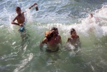 FILE - In this July 22, 2018 file photo, a man's pet dog stands on his shoulder as they take a dip in the ocean with other swimmers near Playita 16 in Havana, Cuba. (AP Photo/Desmond Boylan, File)
