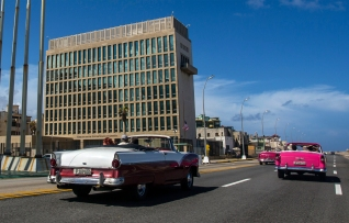 FILE - In this Oct. 3, 2017, file photo, tourists ride classic convertible cars on the Malecon beside the United States Embassy in Havana, Cuba. Doctors treating the U.S. Embassy victims of mysterious, invisible attacks in Cuba have discovered brain abnormalities as they search for clues to hearing, vision, balance and memory damage, The Associated Press has learned. Physicians, FBI investigators and U.S. intelligence agencies have spent months trying to piece together the puzzle in Havana, where the U.S. says 24 government officials and spouses fell ill starting last year in homes and later in some hotels. (AP Photo/Desmond Boylan)