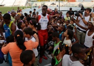 Cuba's Dayron Robles is surrounded by fans after competing in the men's 110m hurdles final of a local athletics competition at the Pan American Stadium in Havana, May 27, 2012. Robles, current world record holder in the event and gold medalist in the Beijing Olympics, told Reuters that he will retire after the 2012 Games in London. Picture taken May 27, 2012. REUTERS/Desmond Boylan (CUBA_