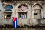 A small picture of Fidel Castro and a Cuban flag decorate a home in Havana, Cuba, Sunday, Nov. 27, 2016. Cuba is observing nine days of mourning for the former president who ruled Cuba for half a century. (AP Photo/Desmond Boylan)