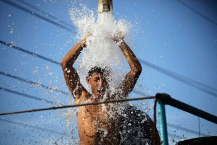 A labourer cools down under water from a supply pump in a truck on the outskirts of Havana, September 5, 2013. REUTERS/Desmond Boylan (CUBA - Tags: SOCIETY ENVIRONMENT TPX IMAGES OF THE DAY) - RTX13952