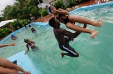 Carmen Gonzalez (R) is carried into a swimming pool by a friend during her quinceanera (coming-out for 15-year-olds) party, January 19, 2013. As nearly all Cuban girls dream of having a quinceanera, the industry that moves around that dream is large, with clients ranging from wealthy Cuban-Americans who travel back to the island to sponsor lavish parties, to regular Cubans who save a few hundred dollars over several years from their monthly $18 state wage. Picture taken January 19, 2013. REUTERS/Desmond Boylan (CUBA)